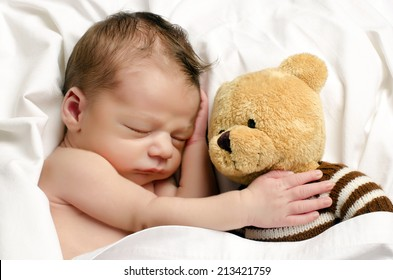 Beautiful innocent newborn sleeping. Adorable little boy relaxing in white sheets after a bath and holding close to him his bear toy