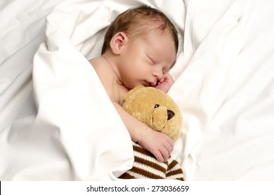 Beautiful innocent newborn sleeping. Adorable little boy relaxing in white sheets after a bath and holding close to him his bear toy. Teddy bear protecting the little baby