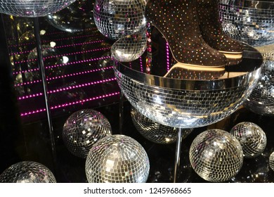 Beautiful inside view to the window of a decorated for Christmas accessory fashion boutique, using glass mirrow balls of a different size made with glued little glass mirrow pieces.