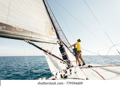 Beautiful inspiring shot of action adventure of sailor or captain on yacht or sailboat attaching big mainsail or spinnaker with ropes on deck of epic boat, sunny summer adventure lifestyle