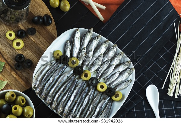 Beautiful, interesting serving on the table from a small fish of the sprat, condiments, olives and decor. The view from the top