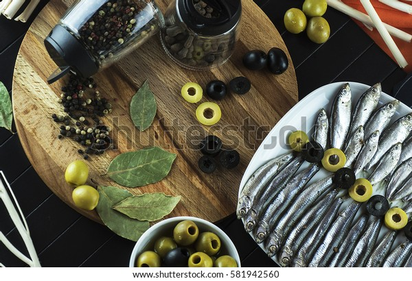 Beautiful, interesting serving on the table of the useful little fish sprat, condiments, olives and decor. The view from the top