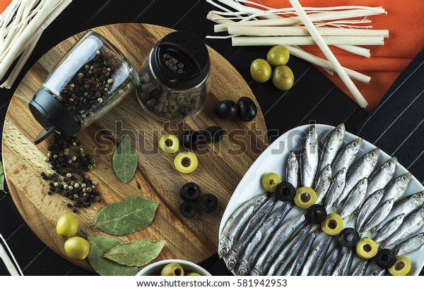 Beautiful, interesting serving on the table of useful, tasty little fish sprat, condiments, olives and decor. The view from the top
