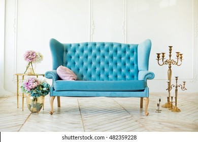 beautiful interior - blue sofa, a glass table and flowers in vases