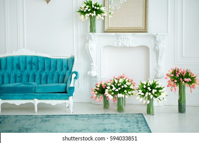 beautiful interior - blue sofa, a mirror and flowers in vases