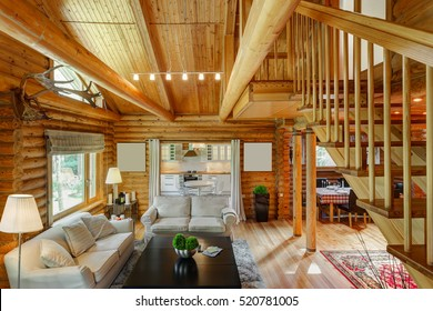 beautiful interior of a living room with views of the kitchen and the second floor in a wooden house