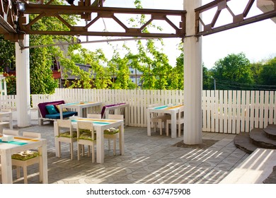 Beautiful interior of the outdoor restaurant of white wood with the sun shining