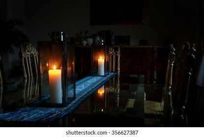 Beautiful interior of a room with a glass table on which there are two burning candles lights dim light from the window