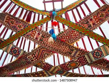 Beautiful interior of traditional Kazakh yurt. Zhelbau - special ornamental woven ribbons of camel wool fixing top of yurt