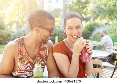 Beautiful interracial couple sipping smoothies during date. Caucasian girl and handsome African man in sunglasses having fun, smiling, talking to each other sitting at street cafe on hot summer day