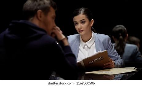 Beautiful interrogator meeting arrested man, investigating crime, mistrust