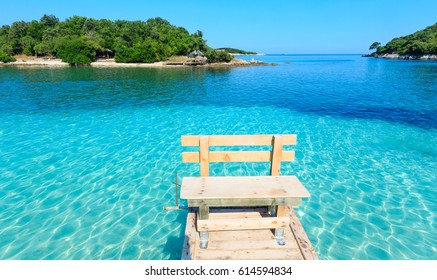 Beautiful Ionian Sea with clear turquoise water, wooden pier and morning summer coast view from beach (Ksamil, Albania).
