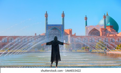Beautiful Iranian girl wearing abaya with arms up happy - Shah (Imam) Mosque (Jameh Abbasi Mosque), Imam mosque in Naghsh-i Jahan Square - Isfahan, Iran,