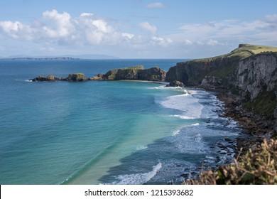 Beautiful Irish coastline. Turquoise Atlantic Ocean meeting with the steep cliffs of Northern Ireland.