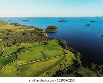 Beautiful Irish landscape, Lake Corrib with many small islands, Green hills with fields separated by stone fences, Clear blue sky.