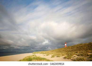 beautiful island with sandy dunes and blue ocean near the lighthouse