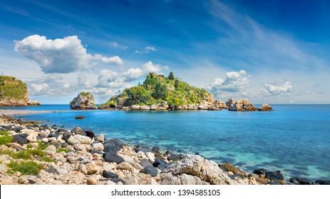 Beautiful Isola Bella small island near Taormina, Sicily, Italy. Narrow path connects island to mainland Taormina beach surrounded by azure waters of the Ionian Sea.