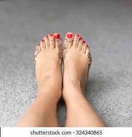 Beautiful isolated henna painted feet of young woman with red nails