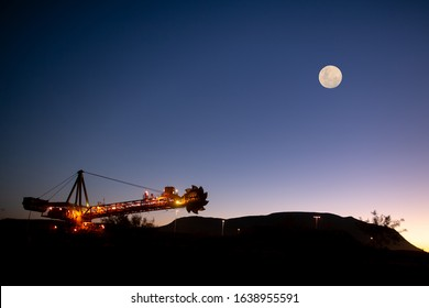 Beautiful isolated massive iron ore reclaimer industry mining heavy duty equipment machinery with full moon at the background