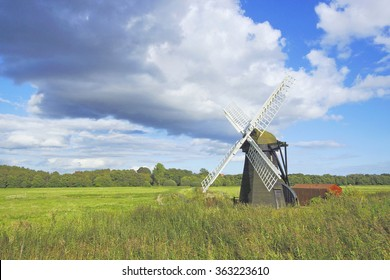 A beautiful isolated windmill with white sails in open countryside under a stormy blue sky in late Summer, Suffolk, United Kingdom
