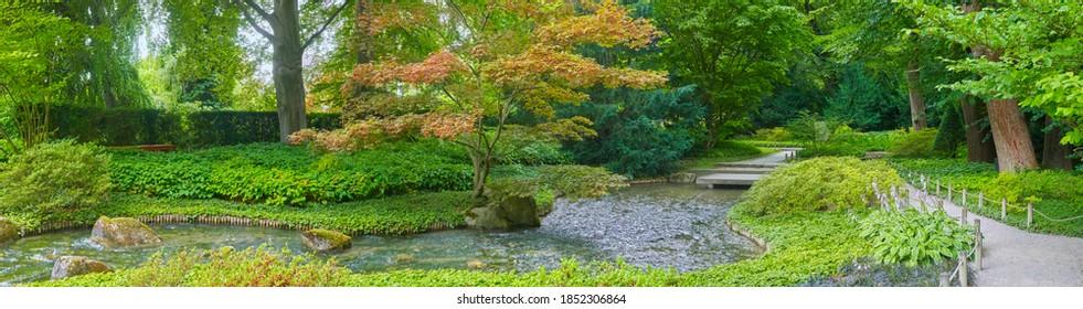 Schöner japanischer Garten mit einem kleinen Bach, im Panoramaformat.