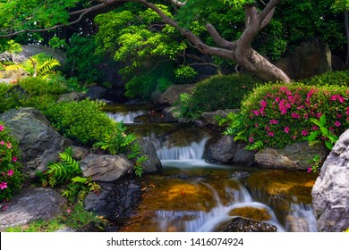 Beautiful japanese garden with small waterfall and blooming rhododendron flowers.