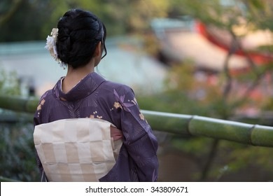Beautiful Japanese girl in a seasonal kimono looking at a scene of a traditional Japanese garden during autumn