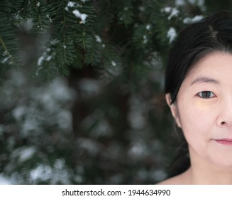 A beautiful Japanese woman looks straight on camera. A half face on dark green background.  A professional artistic photo of an attractive woman on dark snowy texture with space for text.