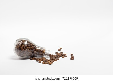 Beautiful jar with coffee beans in the shape of a conventional light bulb lie on a table on a white background
