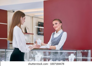 Beautiful jewelry store worker wearing white blouse and grey uniform is showing a necklace designed with blue stones to a smartly dressed female client of the modern jewelry shop.