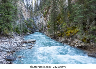 Beautiful Johnston Canyon walkway with turquoise water below, in Banff National Park, Alberta, Canada.  Shot with long exposure to give colorful river a smooth & dreamy effect.