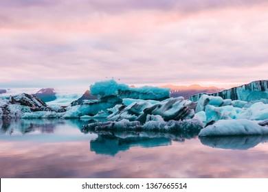 Beautiful Jokulsarlon glacial lagoon sunset sunrise blue icebergs floating  water reflection sky arctic tern birds flying and glacier on the background ice and fire Vatnajokull National Park Iceland