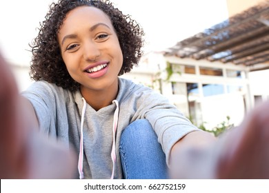 Beautiful joyful african american teenager girl holding smart phone photo camera with hands taking selfies pictures, smiling looking, networking outdoors. Black adolescent woman using technology.