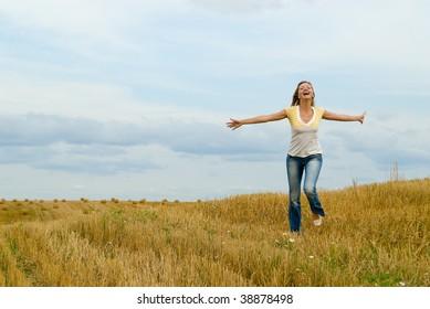 The beautiful joyful girl runs on a field