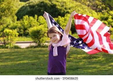 Beautiful joyful girl in a white dress holding a large American flag