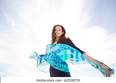 Beautiful joyful mature woman smiling looking, holding silk fabric in the breeze, floating on blue sunny sky, carefree outdoors. Healthy well being recreation lifestyle, plain nature background space.