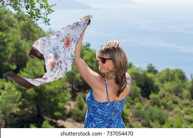 Beautiful joyful mature woman with sunglasses smiling looking, holding silk fabric in the breeze against forest and blue sea on a sunny day. Healthy well being recreation lifestyle.