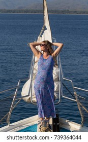Beautiful joyful mature woman with sunglasses on a yacht  enjoying sun. Healthy well being recreation lifestyle.