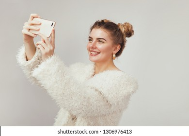 Beautiful joyful woman holding a smartphone and doing selfie against light background