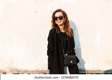 Beautiful joyful young hipster woman with a smile in a black luxurious coat in trendy dark sunglasses with a leather bag in jeans enjoys bright sunlight standing near a white wall. Girl outdoors.