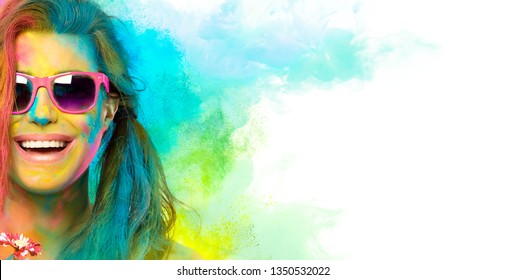 Beautiful joyful young woman celebrating Holi festival of colors, covered in rainbow colored powder with pink sunglasses smiling at camera. Gorgeous party girl having fun with colorful powder