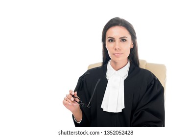 Beautiful judge in judicial robe sitting in armchair and holding glasses isolated on white