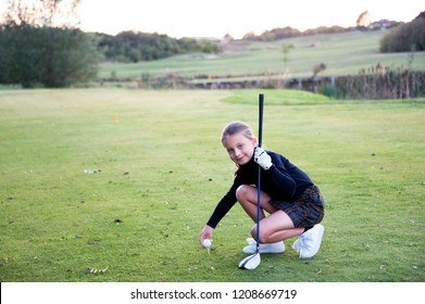 A Beautiful Junior Golfer Teeing it Up. A young girl on the read to becoming a professional golfer.