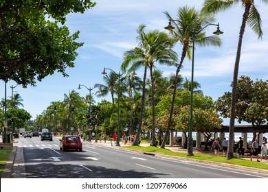 The beautiful Kalakaua Avenue lined with palm coconut trees and the beach in Waikiki Beach Honolulu Hawaii on the 5th of October 2018