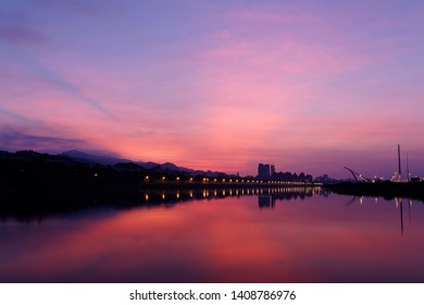Beautiful Keelung River illuminated by morning twilight, with cable-stayed Dazhi Bridge under dramatic dawning sky and riverside street lamp lights reflected in peaceful water, in Taipei City,Taiwan