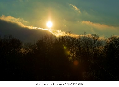 Beautiful Kentucky golden sunset, with sun, clouds and lens flares sinking fast behind a hill with barren trees top on a cold January evening 2019