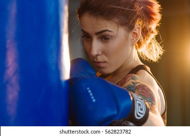 Beautiful Kickboxing woman training punching bag in fitness studio fierce strength fit body kickboxer series. Sexy fighter girl punching actively. Aggressive and ready to fight. Young boxer woman