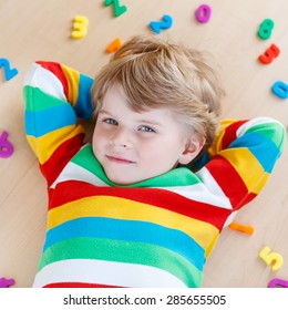 Beautiful kid boy having fun with lots of colorful plastic digits or numbers, indoor. Child wearing colorful shirt and  learning math