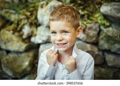 Beautiful kid boy posing in old town
