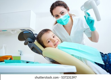 Beautiful kid boy smiling in dentist's chair the office treats teeth. Doctor mask and child looks at camera.